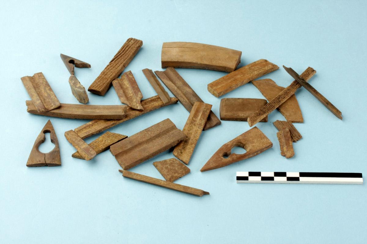 Uit elandgewei gesneden voorwerpen, afkomstig uit het atelier van kruisboogmaker Jans. De plaatjes met een centrale gleuf zijn pijlgeleiders © Agentschap Onroerend Erfgoed