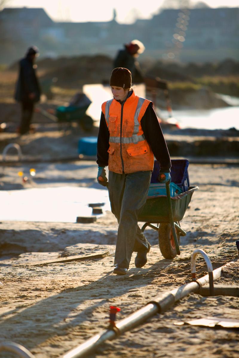 De uitgeschepte grond wordt telkens in stevige plastic bakken met de kruiwagen naar de zeef gevoerd.