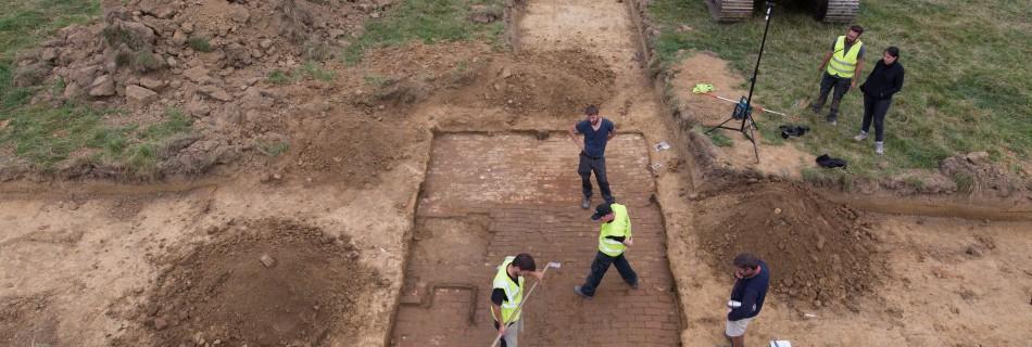 Onder de zoden komt een goed bewaarde vloer in baksteen tevoorschijn. © Universiteit Gent