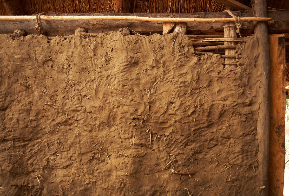 De vlechtwerkwanden worden met een kleimengsel bestreken © Kris Vandevorst, Onroerend Erfgoed
