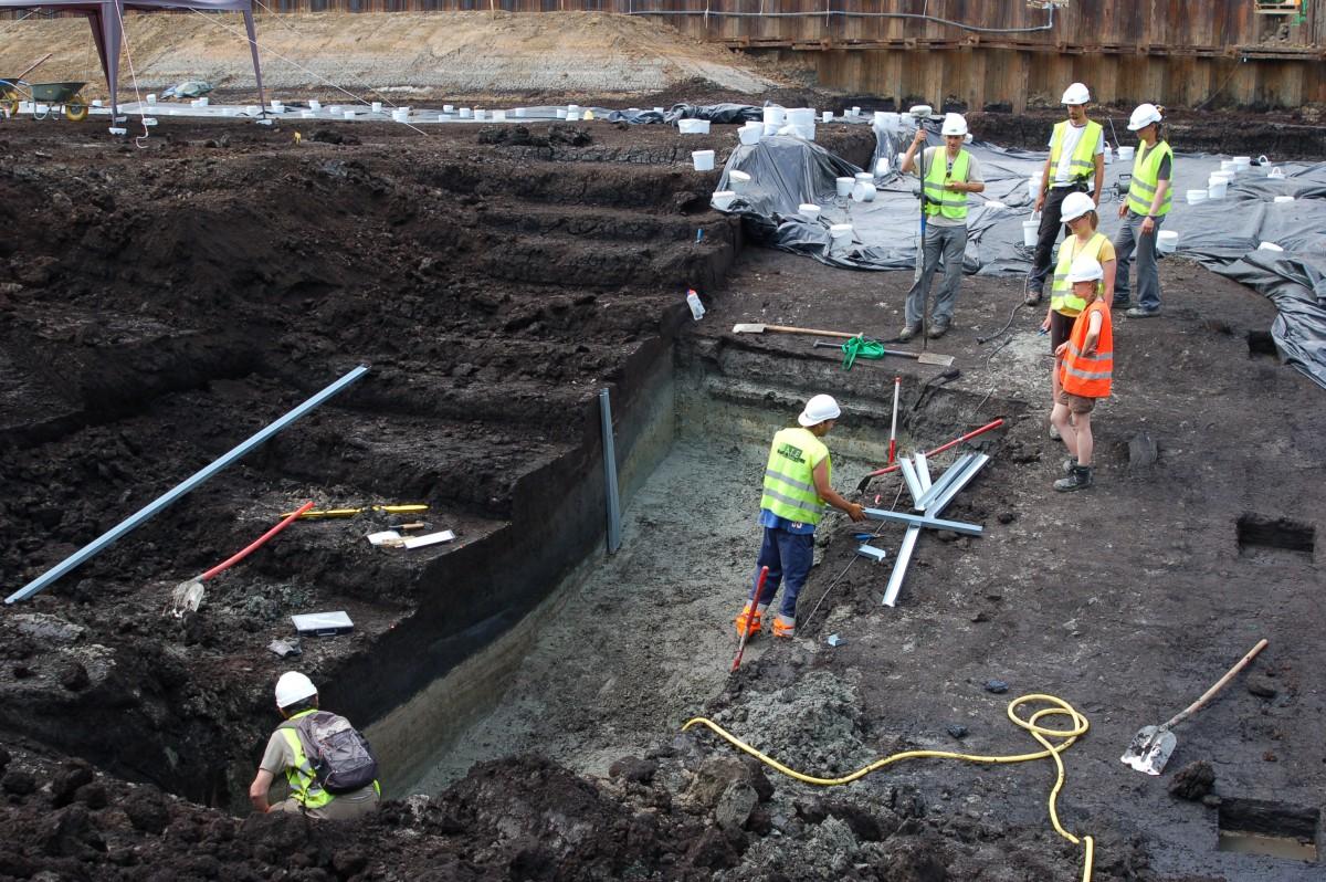 Na het verdiepen in het veen wordt de prehistorische bodem onderzocht door middel van enkele sleuven, om inzicht te krijgen in de bodemopbouw en de verspreiding van prehistorische aanwezigheid © GATE
